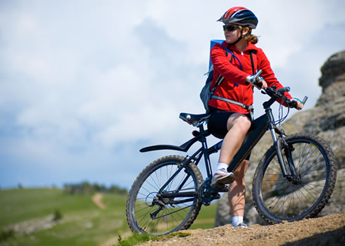A woman mountain biker rests near some rocks