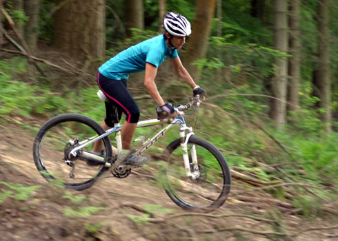 A woman mountain biker descends down a twisty trail